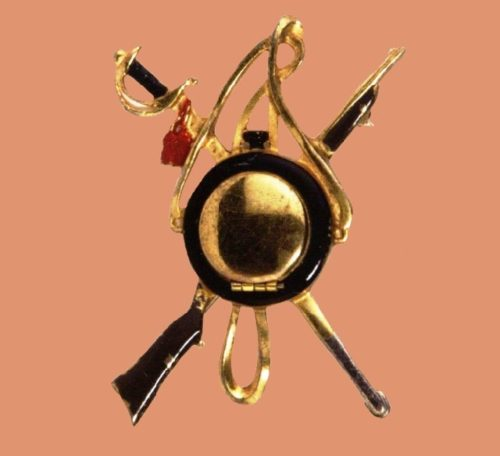 Panoplia, 1940. Designer Victor Silson. Gold plated metal brooch with black, red and brown enamel including a sword, a gun and a sash. 6.5x5cm