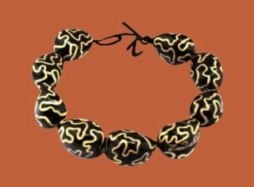 Pebble shaped beads , Zandra Rhodes signature on one of them. Gold tone metal alloy, black cord, black plastic, enamel