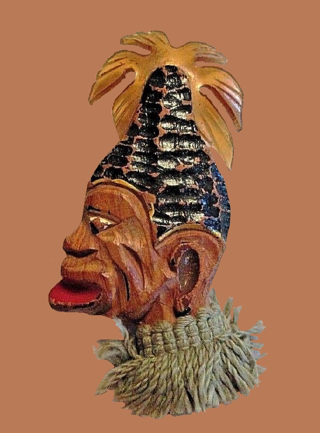 Tribal face brooch. Carved wood, hand painted, a lucite piece at the top and a blue-green trim around the neck. 1940s