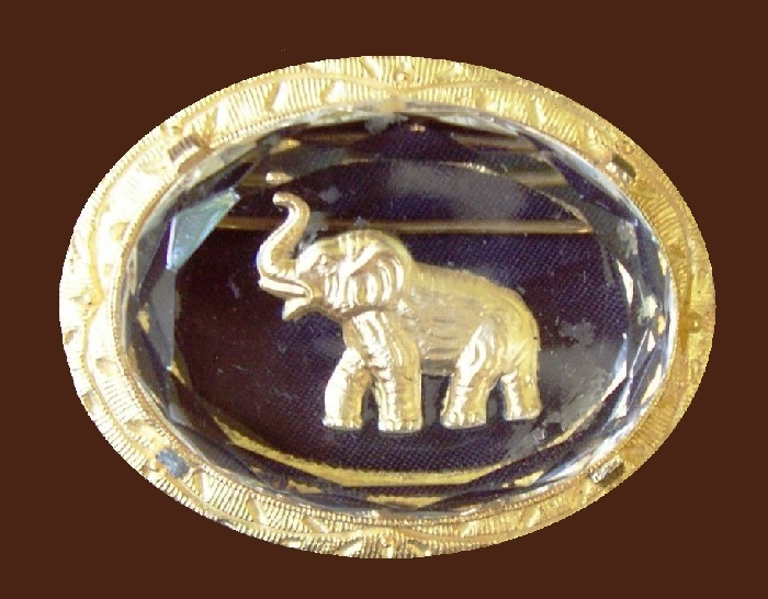 Unique glass oval brooch with the miniature of gold tone elephant in the center