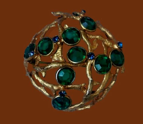 Vintage brooch of gold alloy, covered with gilding. Emerald green crystals and small sapphire crystals