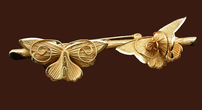 A couple of butterflies on a branch. Textured gold tone pin