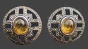 A pair of estate sterling silver clip earrings with amber-colored glass stones in the center