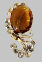Amber glass and rhinestone faceted vintage brooch. Metal of gold tone