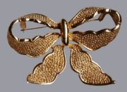 Bow brooch made of gold tone textured jewelry alloy. 6 cm