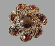 Flower brooch of gold tone metal and brown amber rhinestones