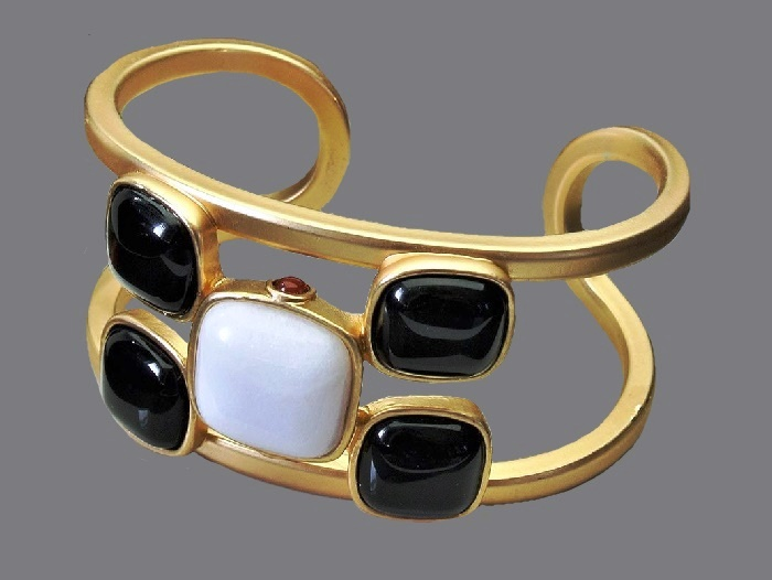 Luxury bracelet. Golden coating, black and white plastic inserts and small red cabochons on the sides of the central white square