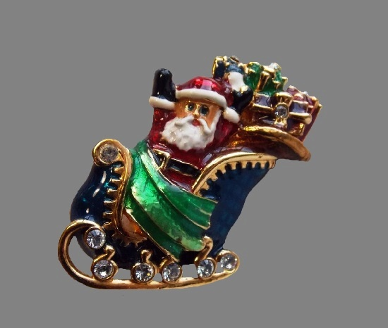 Santa on sledges with gifts vintage brooch. Gold tone metal alloy, enamel, rhinestones. 4 cm. 1990s