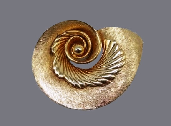 Swirl brooch of gold tone metal