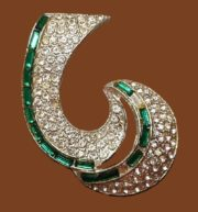 Swirl clip brooch, 1930s. Rhodium plated, pave diamanté rhinestones and emerald green color baguettes
