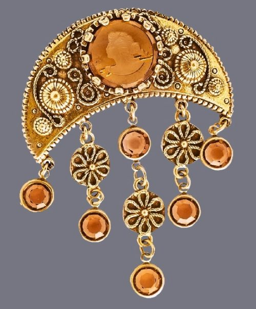 1960s collectible brooch. Jewelry alloy of antique gold color, pendants with bezel crystals, inlay with intaglio of warm honey color. Intaglio - profile of the virgin goddess in glass. Goldette vintage costume jewelry