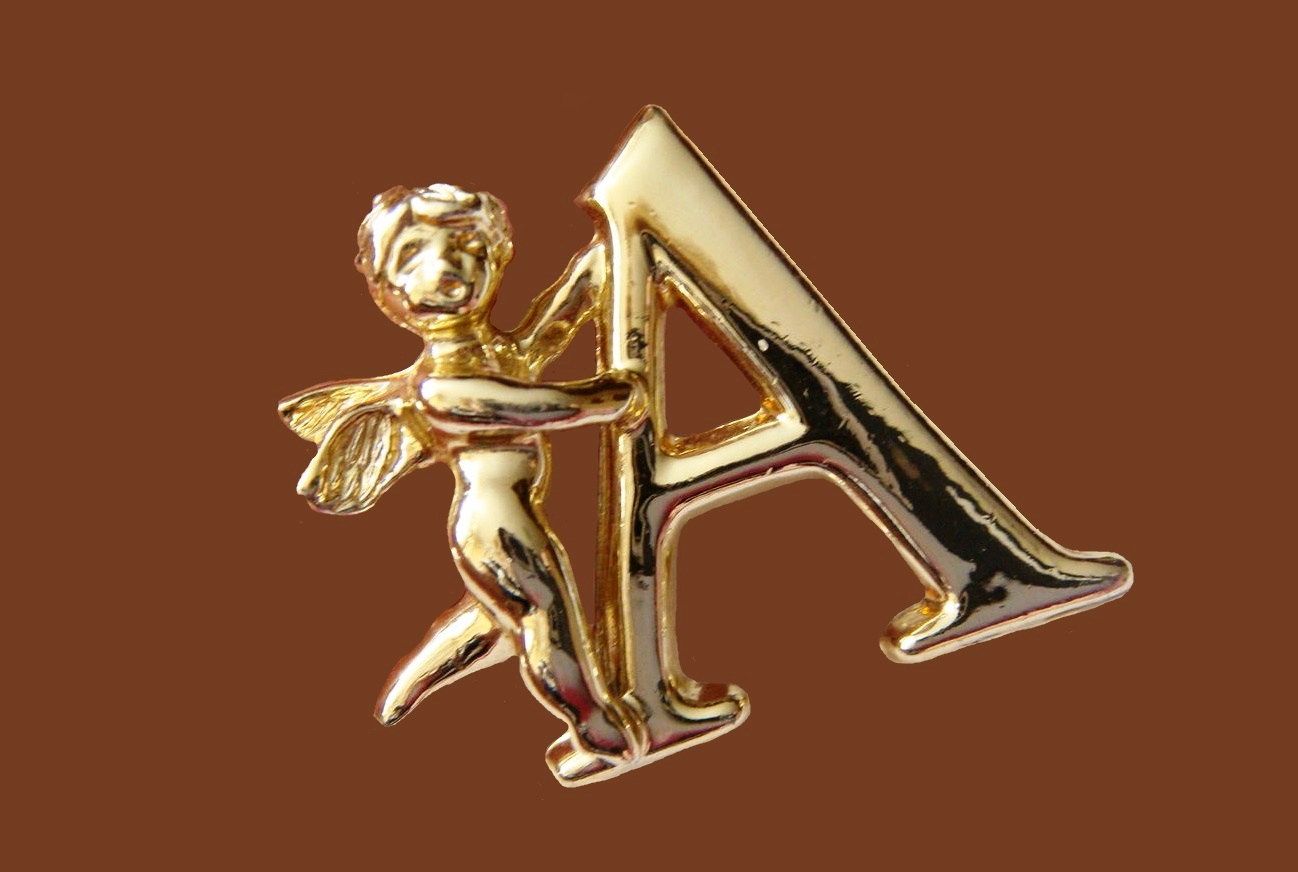 Angel holding letter A brooch pin. Jewelry alloy of gold tone, enamel. 3 cm