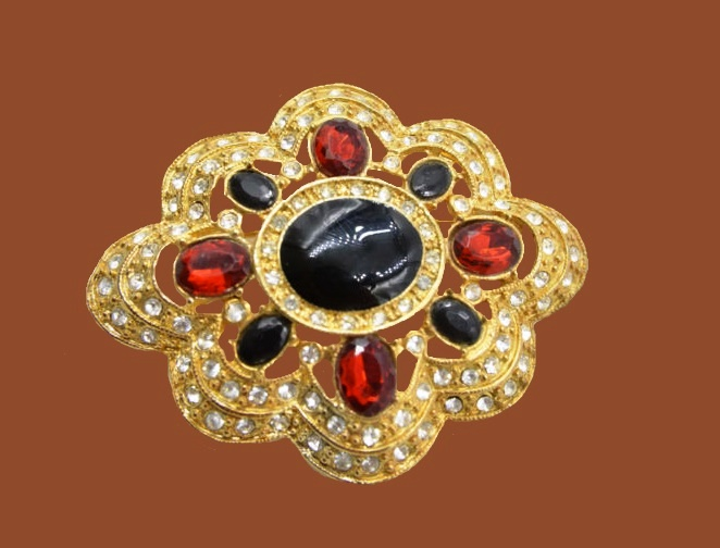 Beautiful brooch of jewelry alloy, rhinestones and cabochons