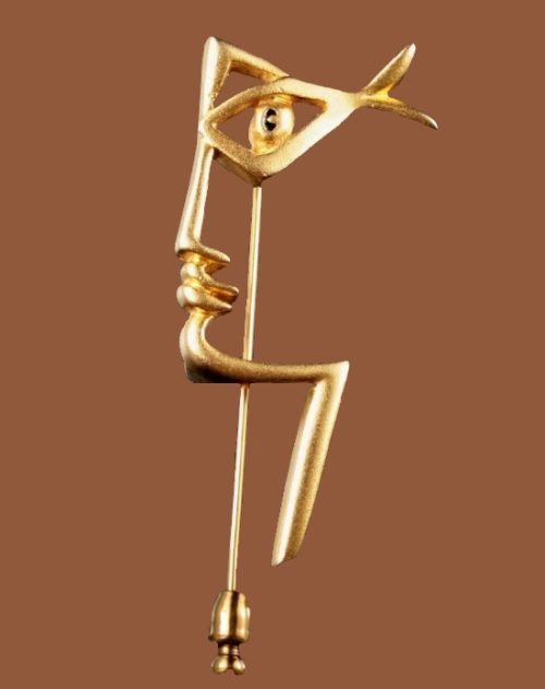 Abstract face gold tone pin designed by Jean Cocteau