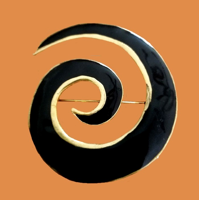 Black swirl enameled gold tone brooch