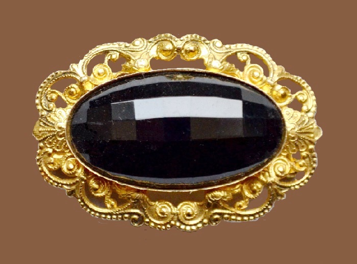 Ellipse brooch of gold tone jewelry alloy with a black cabochon in the center. 4.5 cm