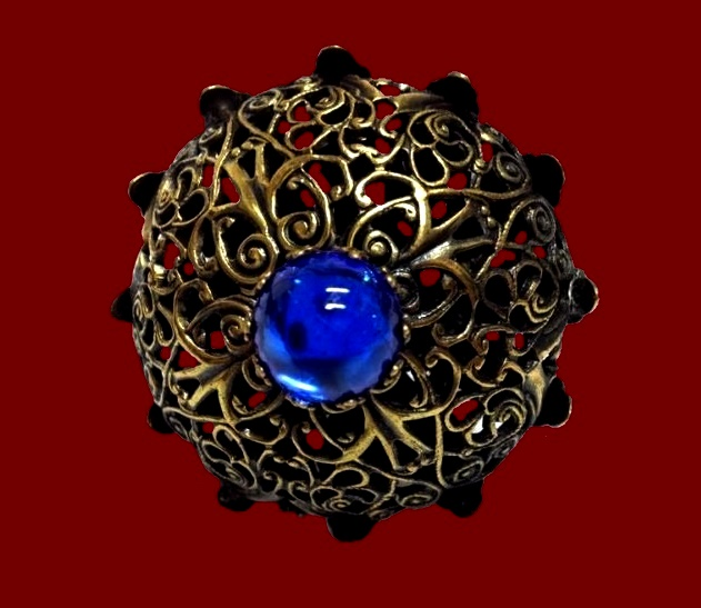 Filigree gold tone ring with faux sapphire in the moddle signed Kim Craftsmen.