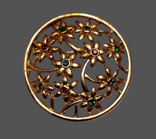 Floral design round brooch. Gold tone metal, rhinestones