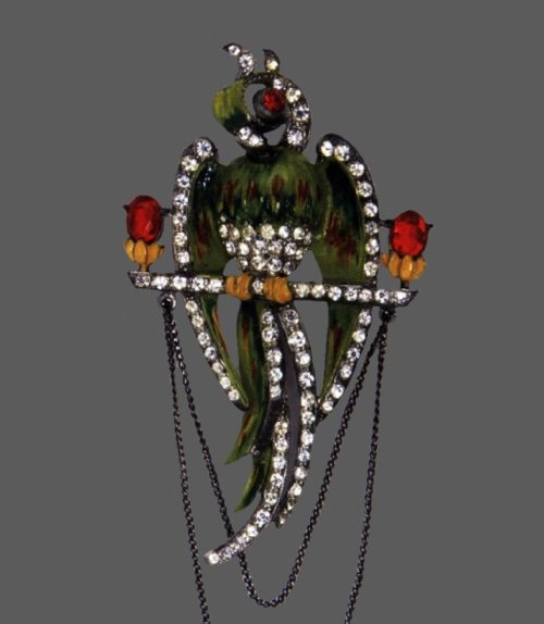 Parrot brooch, 1940. Marked Staret, Manufacturer Staret Jewelry Co., Inc. Pot metal, brown, green and yellow enamel, red stones and rhinestones. 8 cm