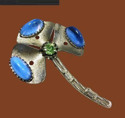 Three petals flower brooch of silver tone with blue cabochons and green rhinestones