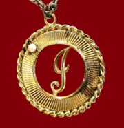 Monogram 'J' pendant. Textured gold tone metal