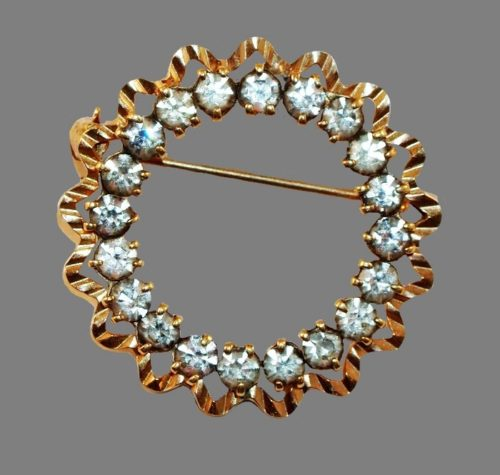 Round gold plated pin with a ruffled trim and clear rhinestones
