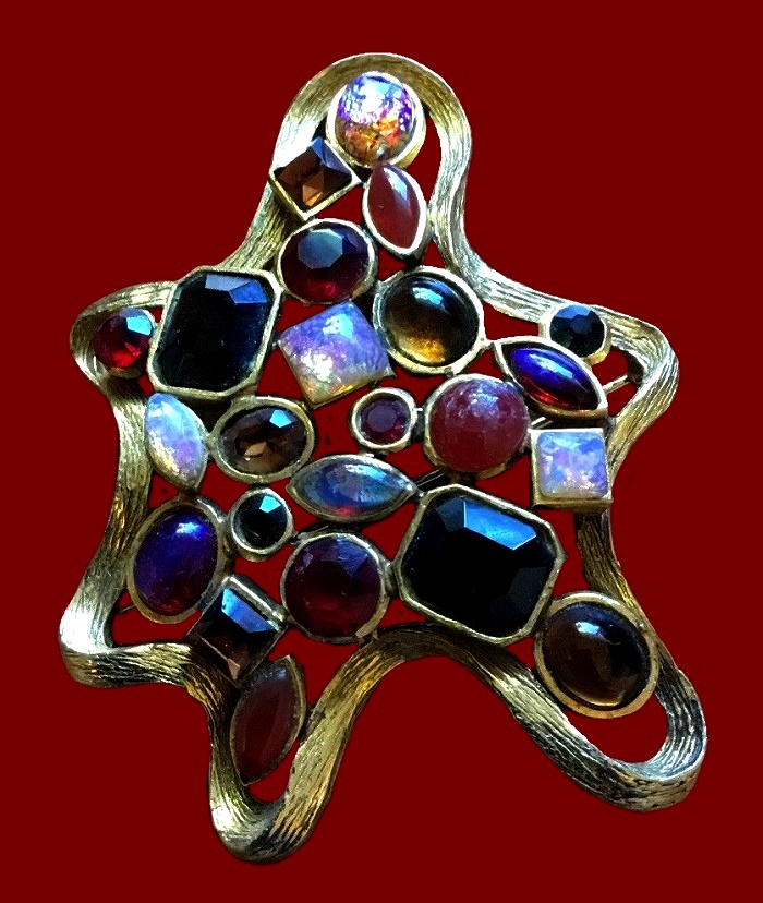 Star shaped gold tone brooch with glass cabochons of ruby, opal and sapphire colors