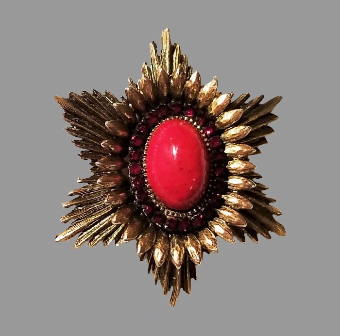 Sunburst gold tone brooch with rhinestones and red glass cabochon in the center