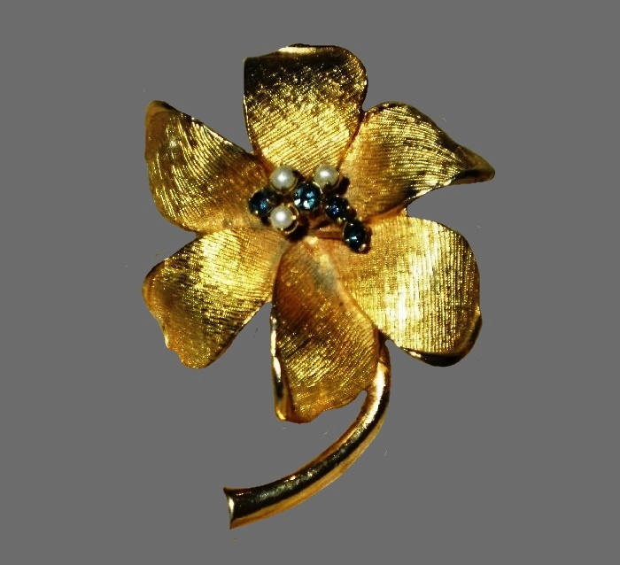 Textured gold tone flower brooch with blue rhinestones and faux pearls