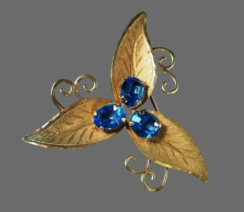 Three leaf brooch. Faux sapphire stones in the center, textured 12 K gold