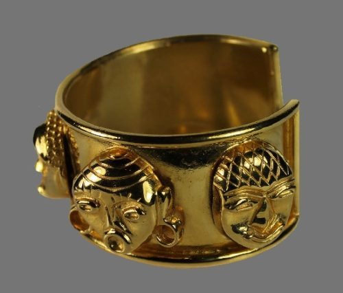 Cuff Bracelet from the 'Traore' collection. Gold tone metal, adorned with 5 masks of African inspiration. Height 3.2 cm, Diameter 5.4 cm