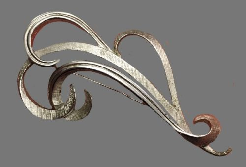 Swirl design brooch of silver tone and crystals. 8 cm