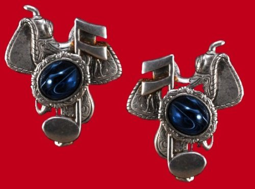 The earrings depicting a saddle, a 16th note and clue cabochon in its setting. 1995