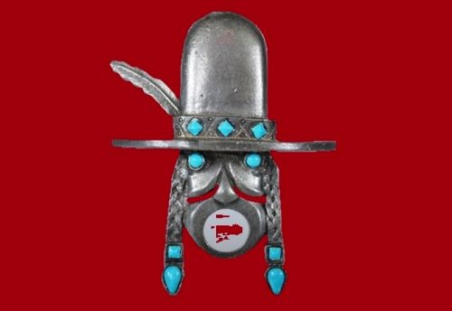 Indian head with traditional braids and feather in a hat. Brass brooch with blue cabochons