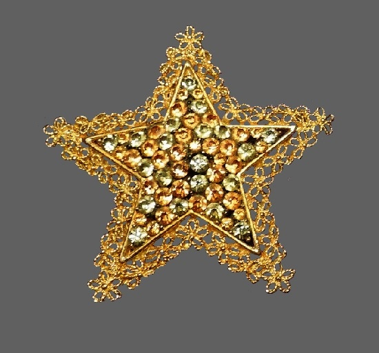 Star brooch. Gold tone metal filigree trim, rhinestones