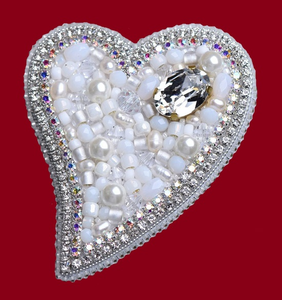 White heart brooch from the collection 'Love is...'. Czech beads, faceted beads, swarovski crystals, Japanese beads, crystal ribbon, strass chain. 7cm