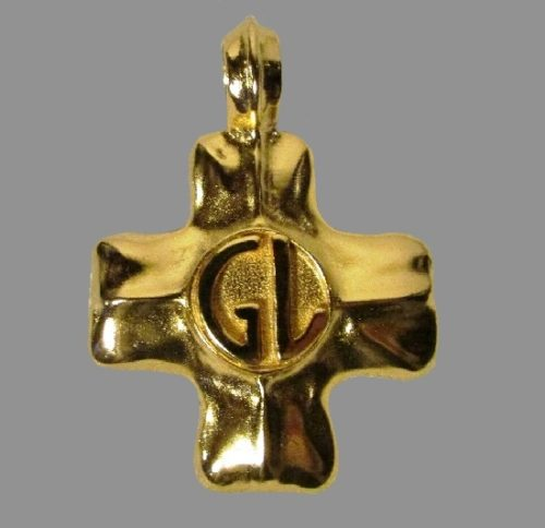 Cross pendant of gold tone with GL initials in the center