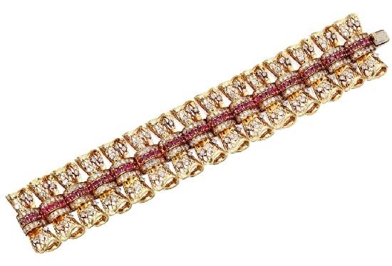 Composed of stylized bow-shaped links of openwork form resembling lace, set with diamonds, accented by round rubies, circa 1945