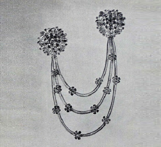 La Fourragere - A creation of John Rubel. Two clips of diamonds, rubies, sapphires mounted in gold with snake-chain studded with flowers of rubies and sapphires. $2275