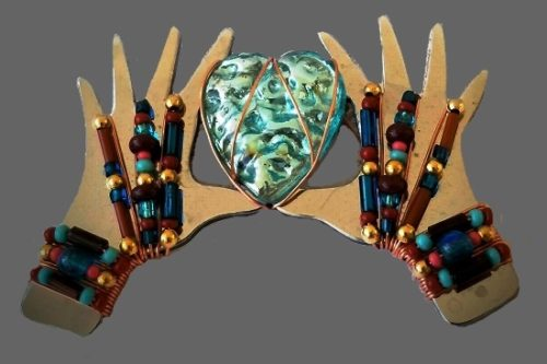 Two hands holding a heart ceramic brooch. 1996