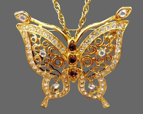 Butterfly brooch pendant. Gold tone metal, purple rhinestones, crystals. 1990s