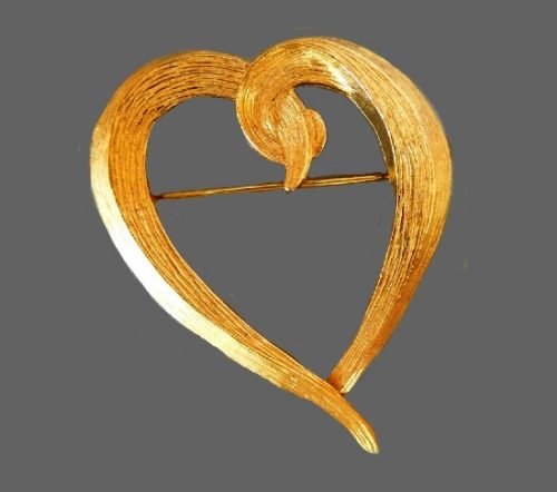 Openwork heart, formed in ribbon style. Textured metal of gold tone
