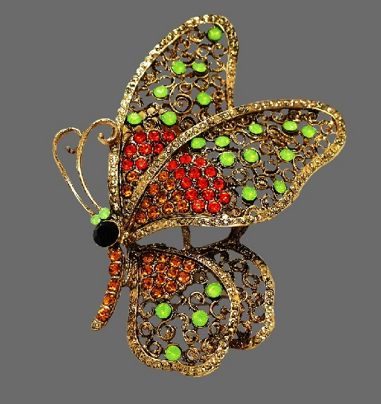 Profile shaped butterfly brooch. Gold tone metal, green crystals