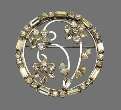 Round shaped floral design brooch pin. Silver tone metal, rhinestones