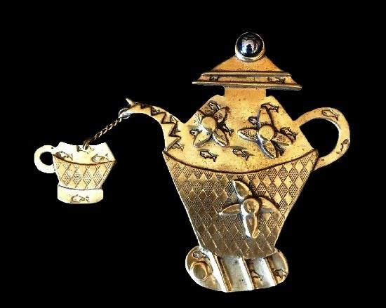 Teapot with a dangling teacup. Textured brass, art glass