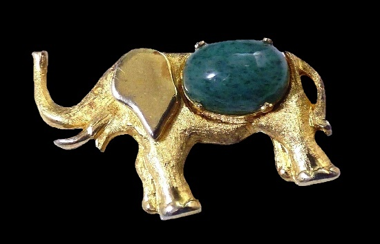 Elephant brooch of gold tone, green cabochon