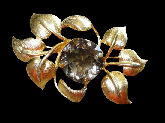 Gold tone brooch pin with a large smokey crystal