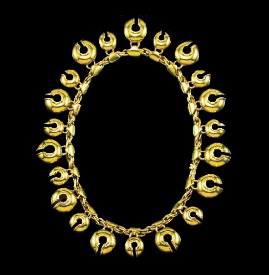 A gold necklace in the shape of a chain supporting a bell-shaped fringe. 1988