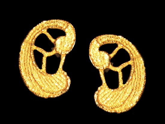 A pair of goldtone textured clip earrings in the Egyptian Revival style