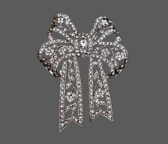 Bow brooch pin. Silver tone metal, clear crystal, rhinestones. 6.5 cm, 1990s